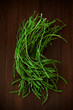 Wild, thin, pencil asparagus bunch on wooden board