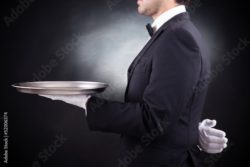 Waiter holding empty silver tray over black background - 52006374