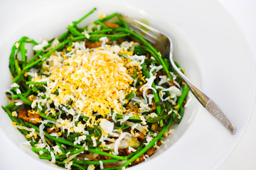 Green wild pencil asparagus with grated egg and chicken, salad