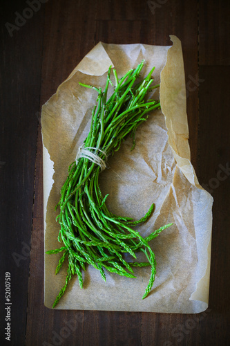 Green wild asparagus bunch on paper and brown wooden desk