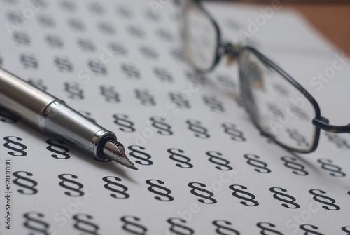 Pióro i okulary na tle w paragrafy - 52008108