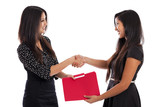 Mixed race businesswomen shaking hands