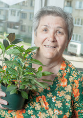 portrait of a senior woman with houseplant