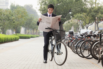 Young businessman sitting on a bicycle and reading the newspaper