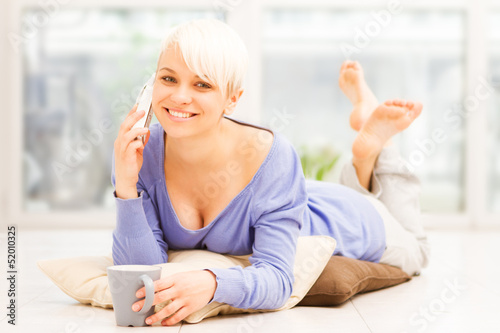 Smiling woman with mug on the floor while phoning