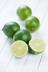 Still life food: ripe limes on wooden boards, vertical shot