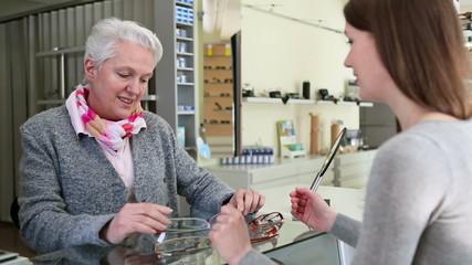 Senior woman buying glasses at optician