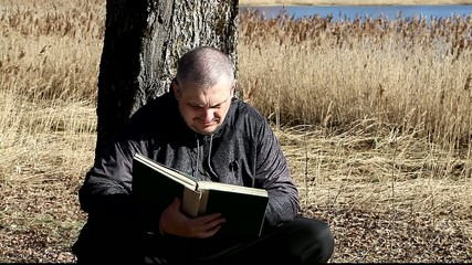 Man reading a book leaning against tree