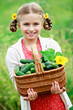 Vegetable garden - lovely girl with picked cucumbers in basket