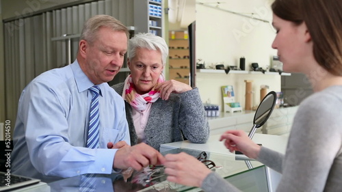 Senior man buying eyeglasses at optician