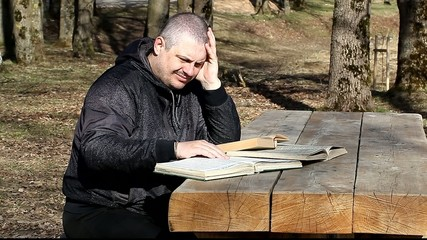 Student reading a book outdoors on a bench