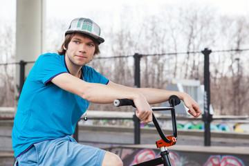 Rider posing with bicycle near ramp