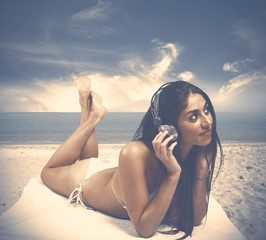 Girl listens to music at the beach