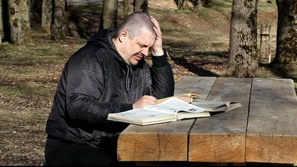Man reading a book outdoors on a bench