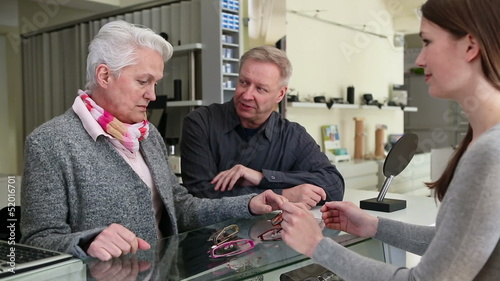 ´Senior couple buying glasses at optician