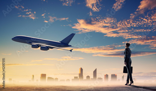 Business woman looking at airplane in sky
