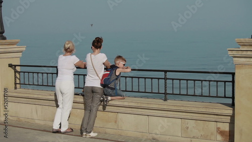 family stands on the waterfront and looking at the sea
