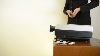 Woman operating a slide projector, with audio, against a wall