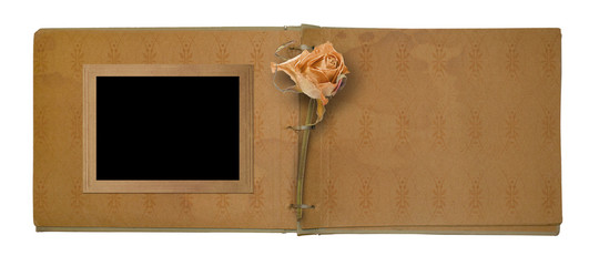 Old photo album with beautiful dried rose isolated on a white ba
