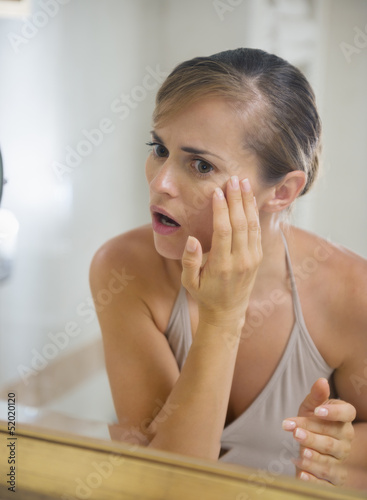 Concerned young woman in bathroom checking skin condition
