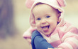 happy smiling baby girl in pink hood with ears