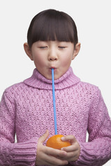 Portrait of young girl drinking an orange with a straw, studio shot