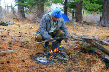 Man beside campfires in wood