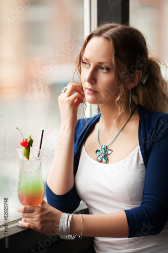 Sad woman with coctail looking out the window