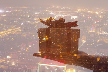 Double exposure of hand holding gift over night cityscape