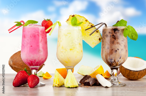 Summer cocktails with pieces of fruit on wooden table