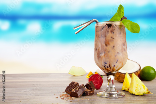 Summer cocktail with pieces of fruit on wooden table