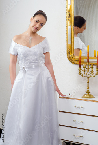 Beautiful bride in wedding dress standing beside mirror