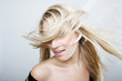 Playful blond woman flicking her hair