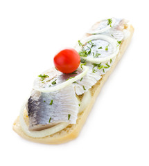 Sandwich with herring, onions, cherry tomato and herbs, isolated