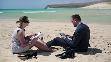 Business people with tablet and documents on beautiful beach
