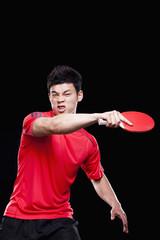 Man playing ping pong, black background