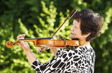 Senior woman performing music outdoors