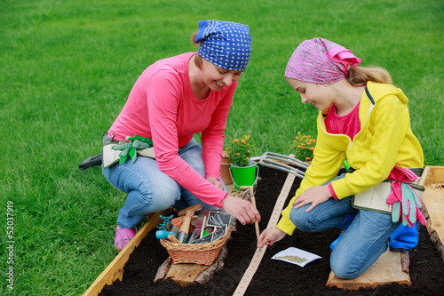 Gardening - woman with girl  sowing seeds into the soil