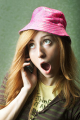 Funny young woman in pink hat gossiping on mobile
