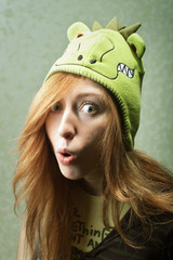 Surprised funny young woman with dragon hat