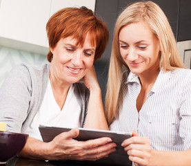 Mother and daughter looking in tablet pc