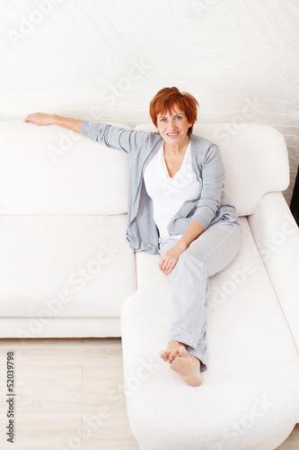 Happy mature woman on sofa