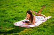 A young woman lying on the grass and reading a book
