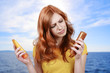 Frau wählt Sonnencreme aus - different suncremes