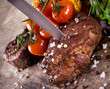 Delicious beef steaks with knife on wooden table