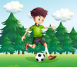 A boy kicking a soccer ball near the pine trees