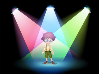 A boy wearing an eyeglass standing on the stage with spotlights