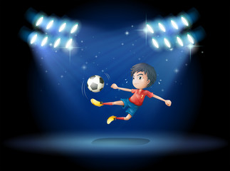 A young boy playing soccer with spotlights