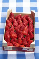 Stiege mit Erdbeeren auf karierter Tischdecke
