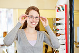 Young woman with new glasses at optician